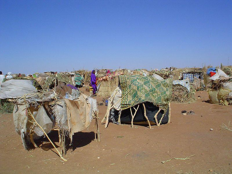 Internally Displaced Persons (IDPs) use sticks and scraps of plastic to construct makeshift shelters at Intifada transit camp near Nyala in South Darfur.