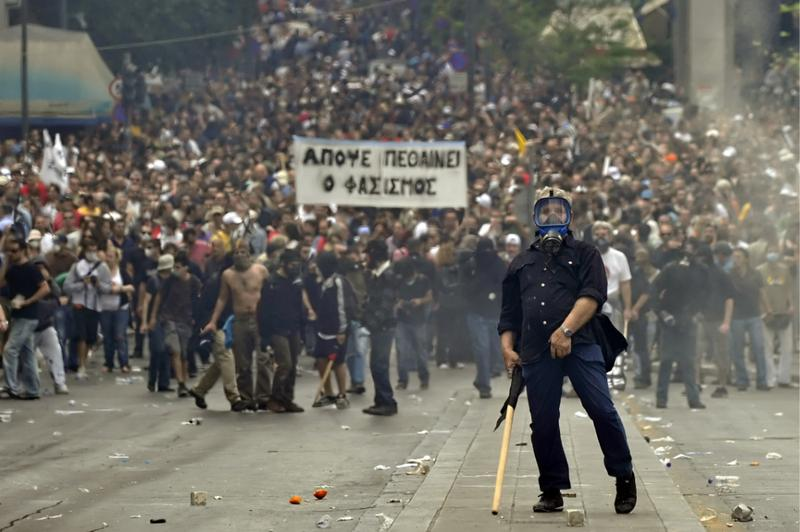 A protestor gestures to police near the Parliament building in the center of Athens.