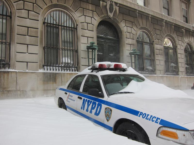 A police car is snowed under in Brooklyn.
