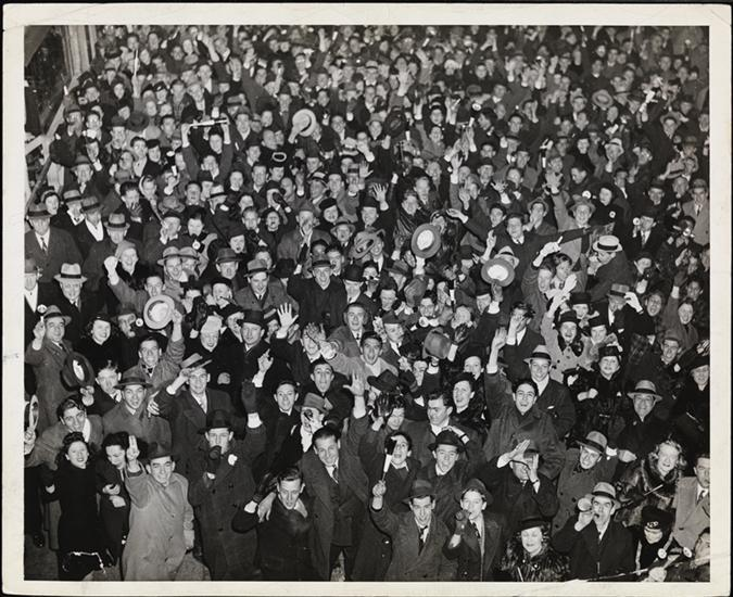 Crowd cheering and holding noise-makers, possibly on New Years, ca. 1945.