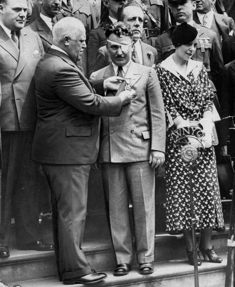 Mayor John P. O'Brien pinned a gold medal on aviator Wiley Post, July 26, 1933. Post's wife Edna Mae is on the right behind the WNYC microphone.