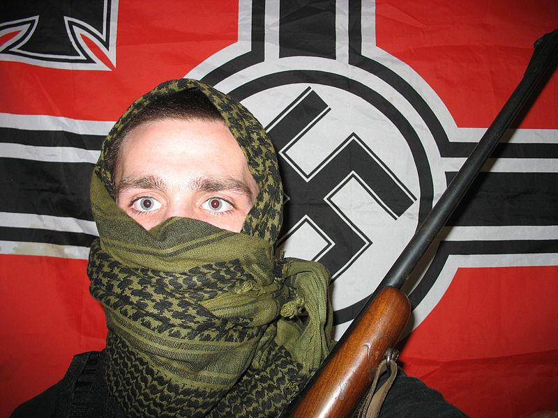 A man holding a rifle in front of a flag with a swastika on it.