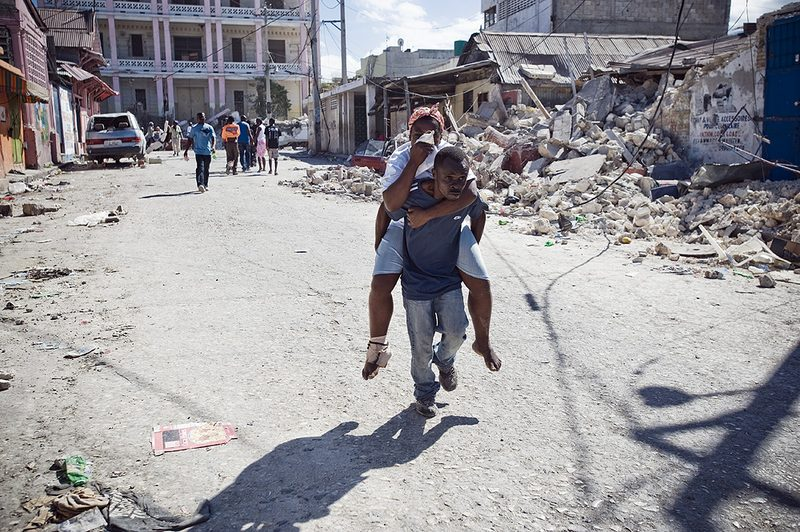 Man carries a woman to a makeshift clinic on his back on Saturday January 16, 2010 in Port-au-Prince, Haiti.