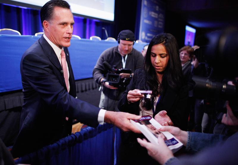 Former Massachusetts Governor Mitt Romney gives away paperback copies of his book, 'No Apologies,' after addressing the Conservative Political Action Conference in February 2011.