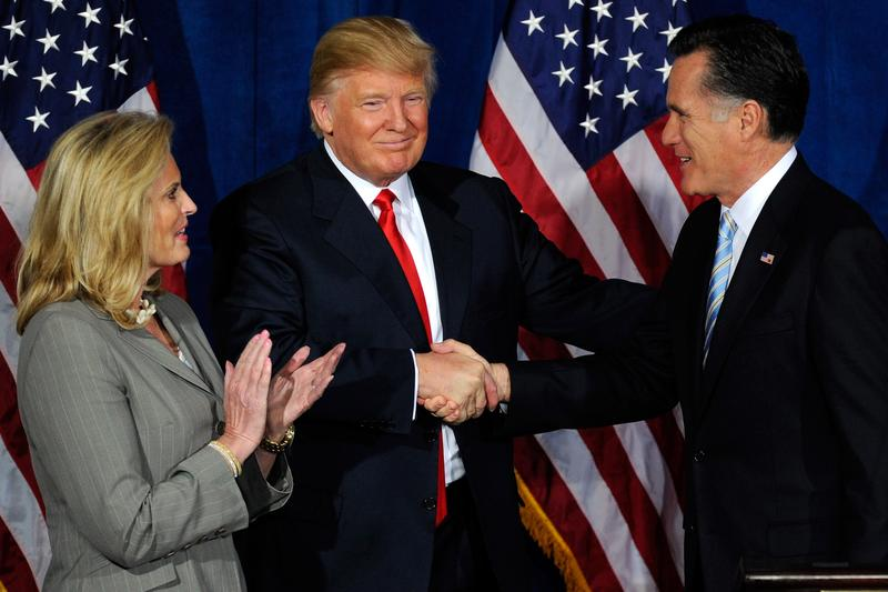 Ann Romney looks on as Donald Trump and Republican presidential candidate, former Massachusetts Gov. Mitt Romney shake hands during a news conference held by Trump to endorse Mitt Romney for president