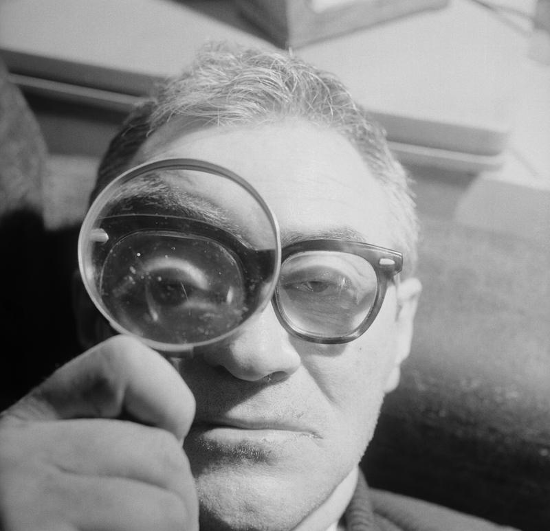 James T. Farrell peering through a magnifying glass, February 16, 1963.