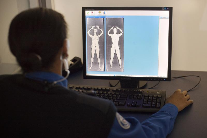 A TSA officer demonstrates what the images from the Advanced Imaging Technology unit look like at John F. Kennedy International Airport's Terminal 8 passenger security checkpoint on October 22, 2010