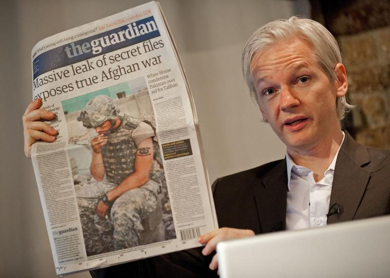WikiLeaks Founder Julian Assange holds a copy of today's Guardian newspaper