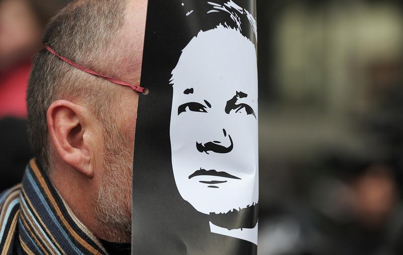 A demonstrator wears a mask depicting the face of the WikiLeaks founder, Julian Assange, during a protest over his arrest, outside the City of Westminster Magistrates' Court in central London