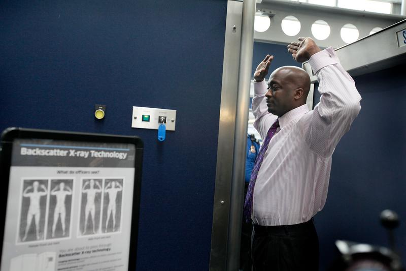 A Transportation Security Administration (TSA) volunteer demonstrates a full-body scanner at O'Hare International Airport