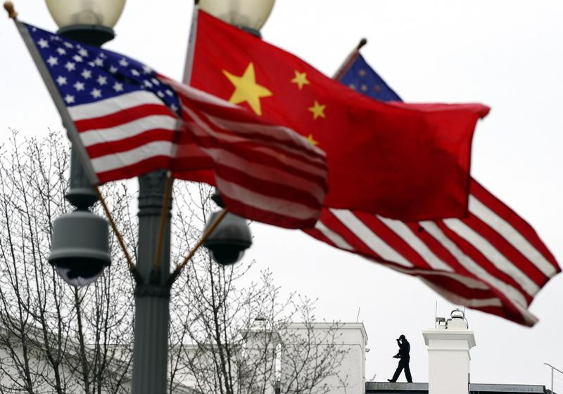 A Secret Service agent guards his post on the roof of the White House as a lamp post is adorned with Chinese and US national flags in Washington, DC, on January 17, 2011.