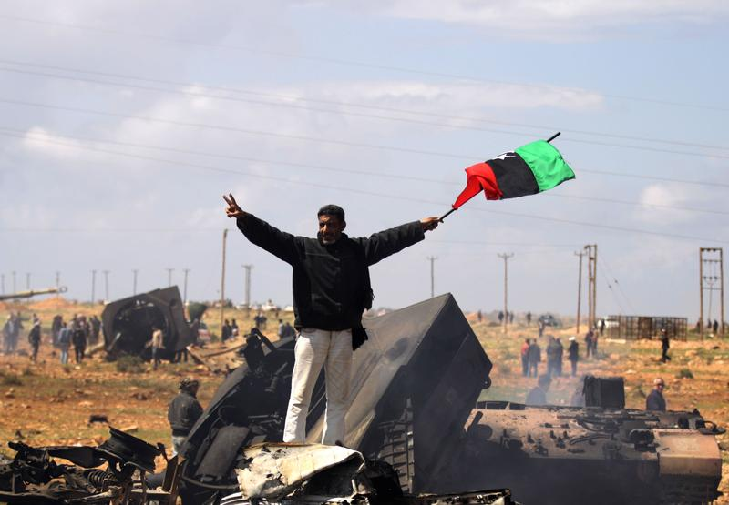 A Libyan rebel waves the rebellion flag as he stands over wrecked military vehicles belonging to Moammer Khaddafi forces hit by French warplanes on March 20, 2011.