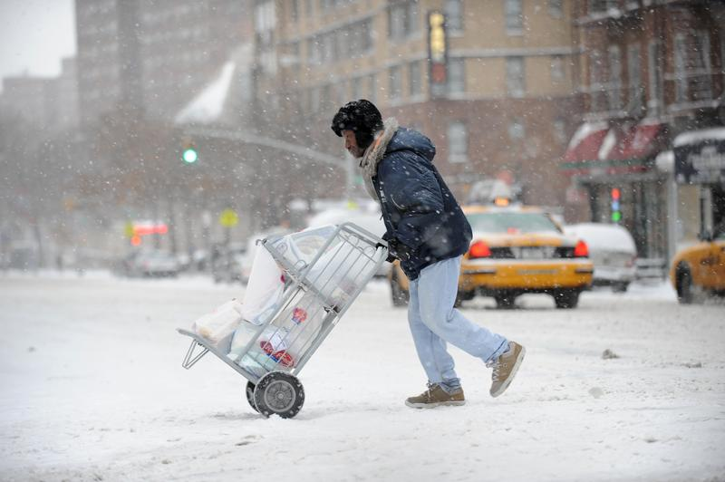 A delivery man crosses Third Avenue on the east side of Manhattan January 21, 2012 during the first snow storm of the year in New York.