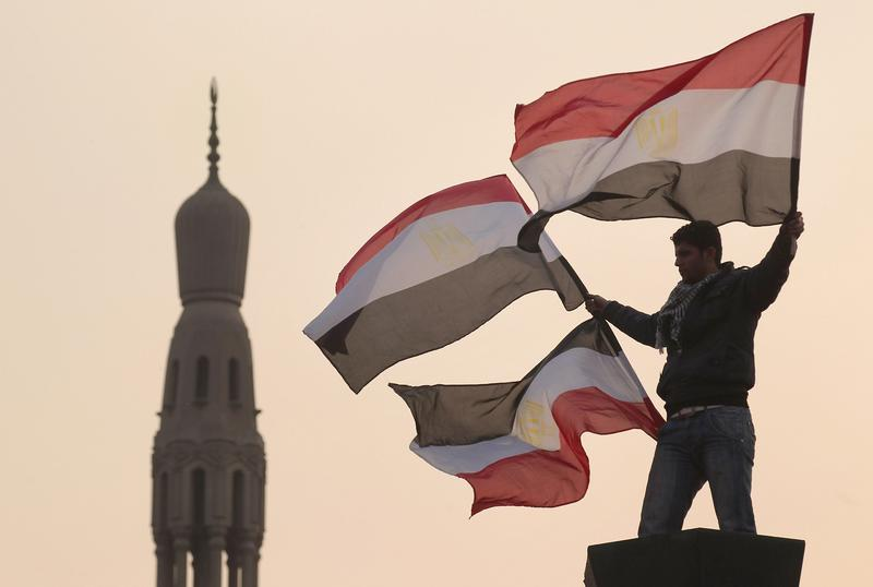 A youth waves Egyptian flags from a lamp post in Tahrir Square on February 1, 2011 in Cairo, Egypt.