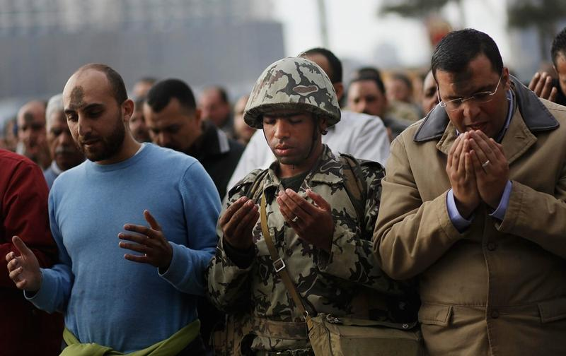 An Egyptian Army soldier prays along with anti-government protesters during the afternoon in Tahrir Square January 30, 2011 in Cairo, Egypt.