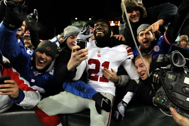 Kenny Phillips #21 of the New York Giants celebrates with fans after a touchdown against the Green Bay Packers.