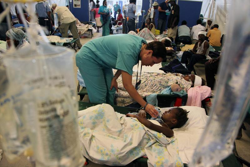 An injured child is cared for by an expatriate Haitian nurse who flew in from Miami with a medical team.