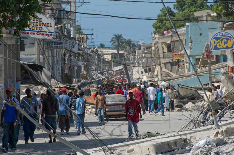 People wander the streets in front of the remains of a boarding school in the downtown area in Port-au-Prince, Haiti.