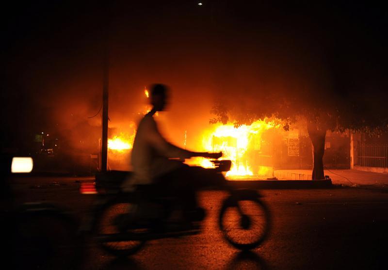 A Pakistani man rides past a burning shop in Karachi, Pakistan.