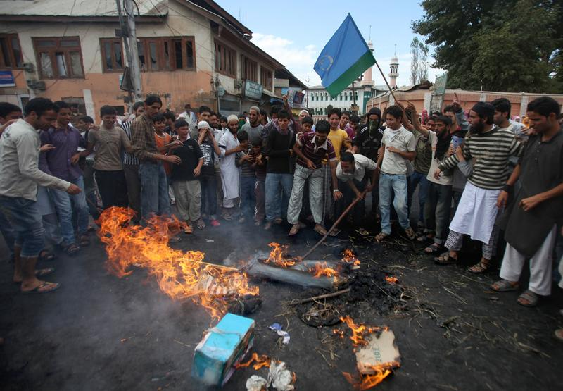 Kashmiri protesters beat the burning remains of an effigy representing US President Barack Obama during a protest in Budgam on the outskirts of Srinagar on September 13, 2010.