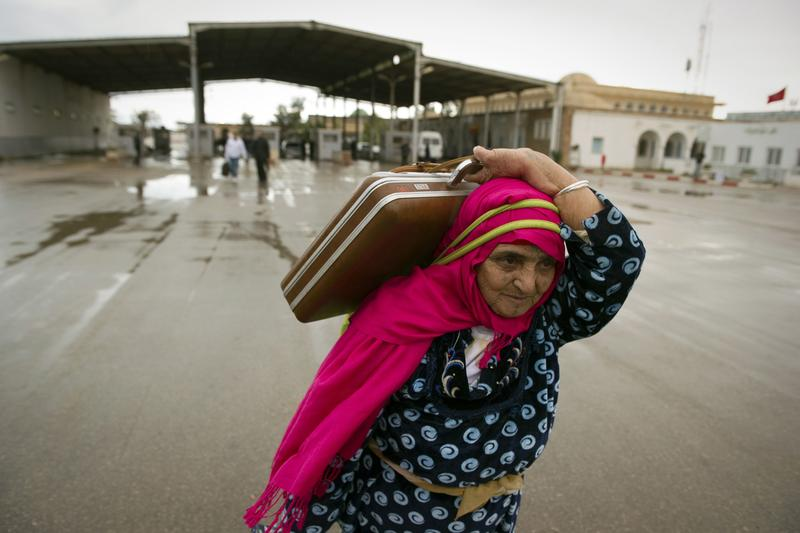 A Tunisian woman carries her bags past the Ras Jdir border post between Libya and Tunisia, near the Tunisian city of Ben Guerdane, after leaving Libya on February 23, 2011