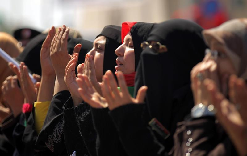 Libyan women perform firday's noon prayer in Benghazi on March 25, 2011 as coalition forces launched a seventh day of air strikes against the regime of Libya's Moammar Gadhafi