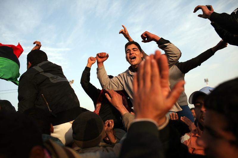 Men who have recently arrived from Libya celebrate at the border while waiting to be assigned to buses to take them to a transit camp on February 26, 2011 in Ras Jdir, Tunisia