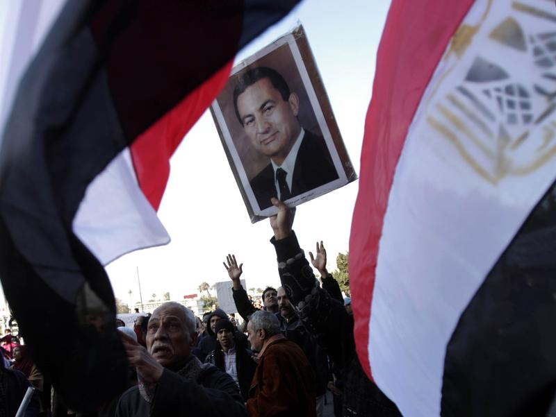 Supporters of President Mubarak wave their national flag as they hold a rally in support of the veteran leader in Cairo on February 2, 2011.