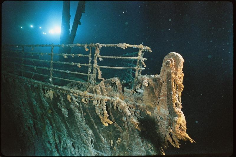 Bow railing of <em>R.M.S. Titanic</em> illuminated by Mir 1 submersible behind the  forward anchor crane. Rustcicles' slant shows the direction of the current.