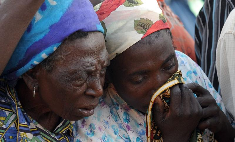 A woman wipes a tear after dead bodies mostly women and children were killed during religious clash between natives of Dogo Nahawa and Hausa Fulani