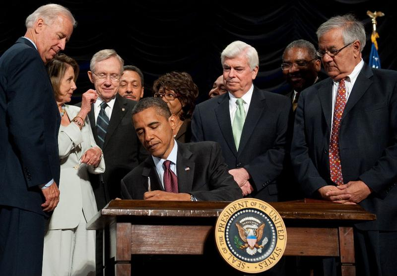 U.S. President Barack Obama signs the Dodd-Frank Wall Street Reform and Consumer Protection Act alongside members of Congress, the administration and U.S. Vice President Joe Biden
