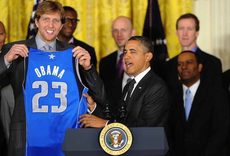 Dirk Nowitzki of the 2011 NBA Champion Dallas Mavericks presents President Obama with a custom jersey.