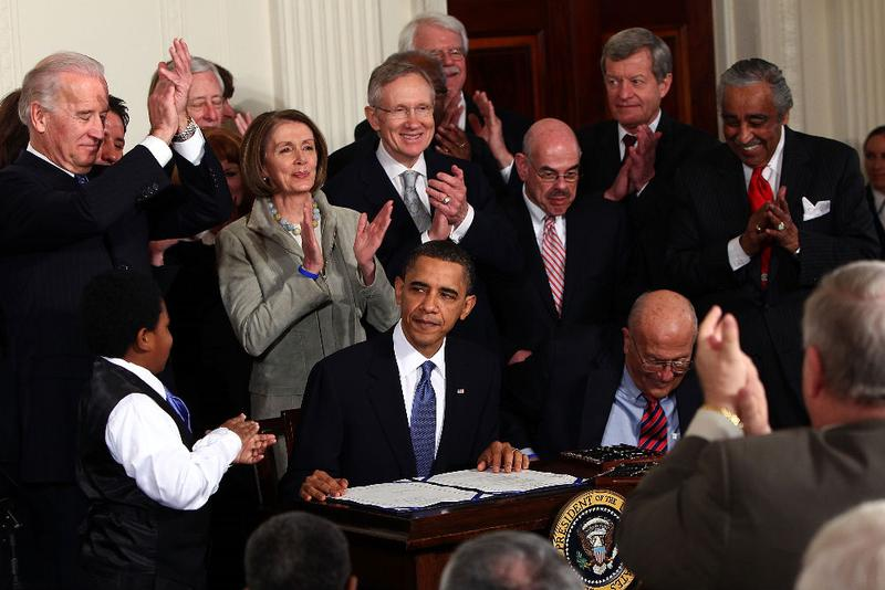 U.S. President Barack Obama (C) is applauded after signing the Affordable Health Care for America Act during a ceremony with fellow Democrats in the East Room of the White House