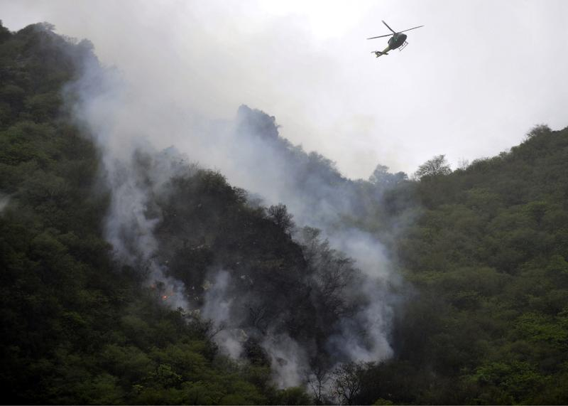 A Pakistani rescue helicopter flies over smoke and wreckage of a crashed passenger plane in The Margalla Hills on the outskirts of Islamabad on July 28, 2010.