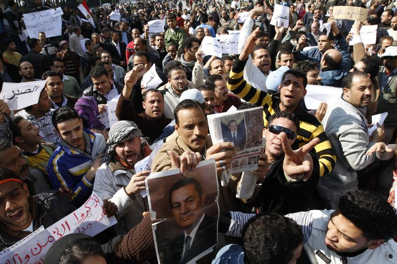 Supporters of Egyptian President Hosni Mubarak shout slogans and hold signs during a rally to show their allegiance for the embattled leader in Cairo on February 2, 2011.