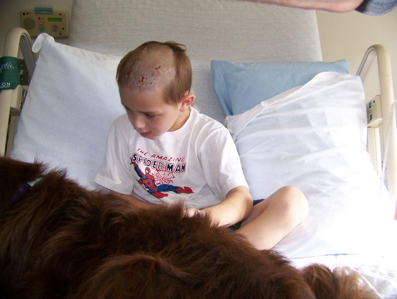 Samwise Leszczynski, who suffered a traumatic brain injury, pets his dog in his hospital bed.