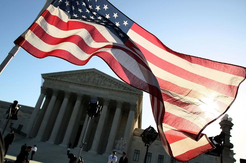 A person carries an American flag while marching in favor of the Patient Protection and Affordable Care Act in front of the U.S. Supreme Court.