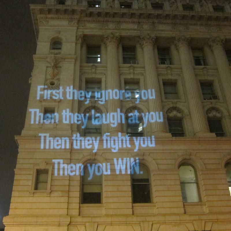 Occupy Wall Street slogans projected on a building near Centre Street.