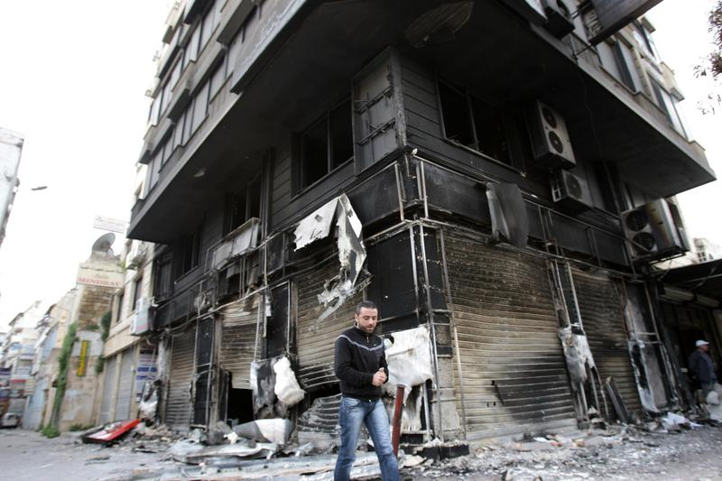 A man walks past a burnt-out building in the Northern city of Latakia, some 350 km northwest Damascus on March 27, 2011.