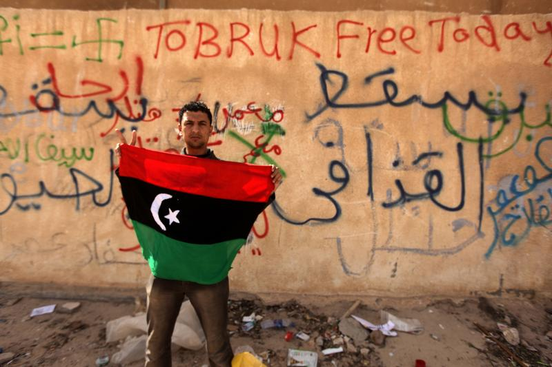 A Libyan anti-government protester holds his old national flag in front of a wall covered with graffiti against Libyan leader Moammer Gadhafi in the eastern city of Tobruk on February 24, 2011.