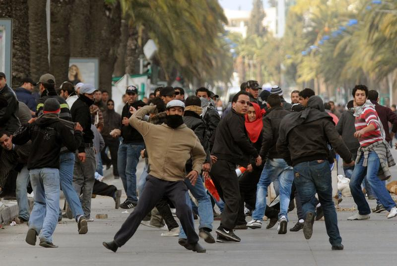 A Tunisian demonstrator throws a rock during clashes with security forces on Mohamed V avenue in Tunis on January 14, 2011.