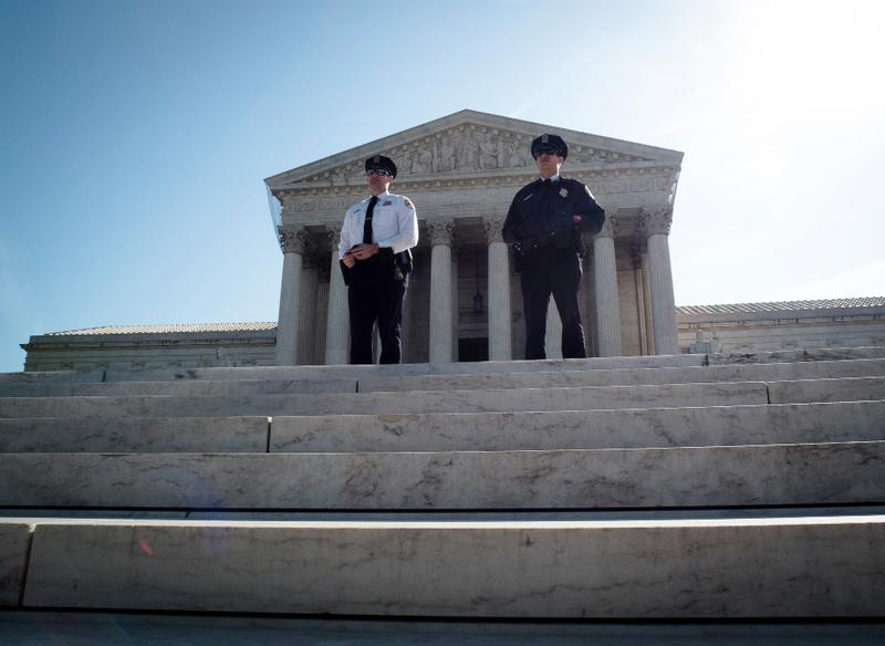 Two policemen guard outside the US Supreme Court on the third day of oral arguements over the constitutionality of the Patient Protection and Affordable Care Act on March 28, 2012 in Washington, DC.
