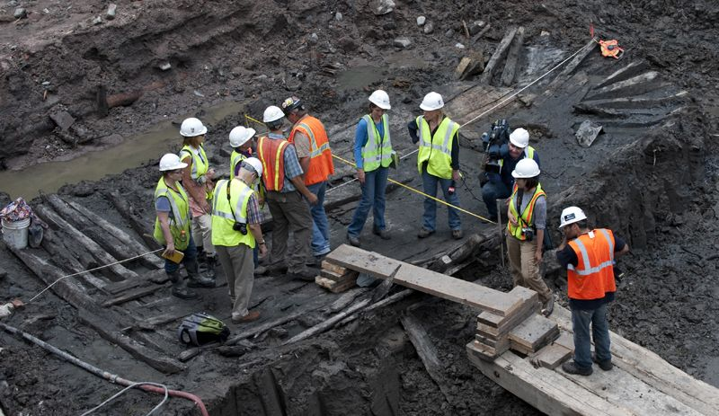 Workers and members of the media inspect the hull of a late 18th or early 19th century ship found at the World Trade Center site