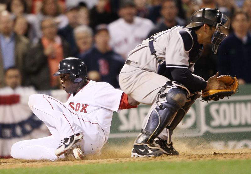 Mike Cameron #23 of the Boston Red Sox slides home safely past Jorge Posada #20 of the New York Yankees on April 4, 2010 during Opening Night at Fenway Park in Boston