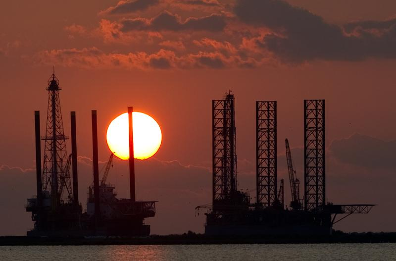 The sun sets behind two under construction offshore oil platform rigs in Port Fourchon, Louisiana, June 14, 2010, as cleanup continues on the BP Deepwater Horizon oil spill.