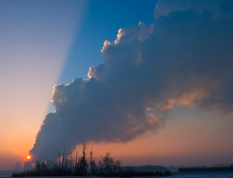 The sun goes up over the steaming cooling towers of the lignite power plant of Jaenschwalde, on February 22, 2011.