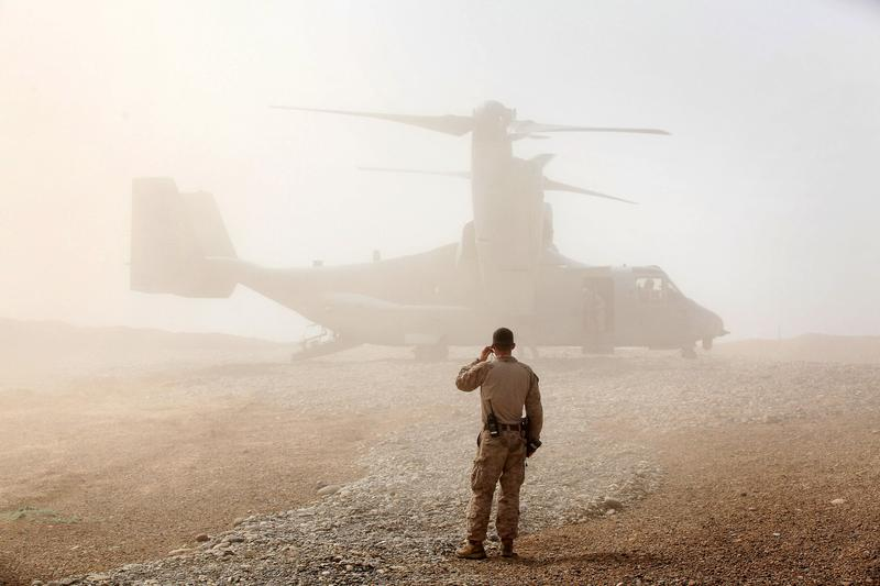 A U.S. Marine watches as an Osprey carrying U.S. Secretary of Defense Leon Panetta arrives March 14, 2012 at Forward Operating Base Shukvani, Afghanistan.