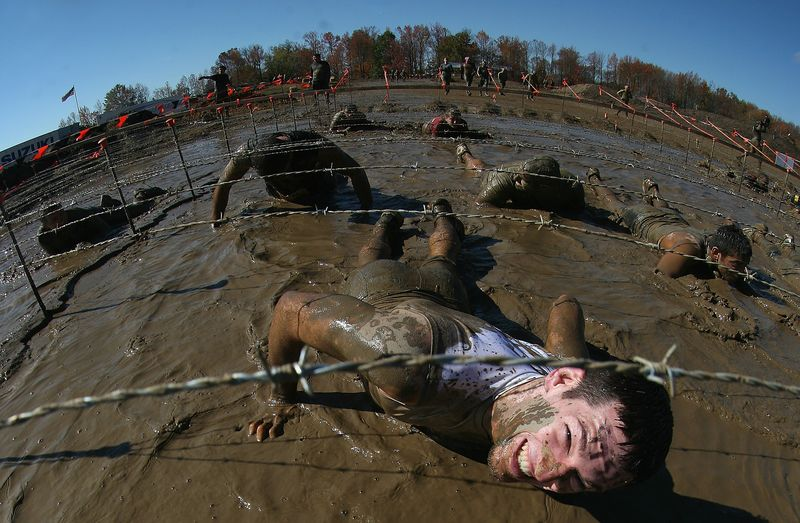 Participants go through the Kiss of Mud obstacle at the Tough Mudder event at Raceway Park on October 21, 2012 in Englishtown, New Jersey.