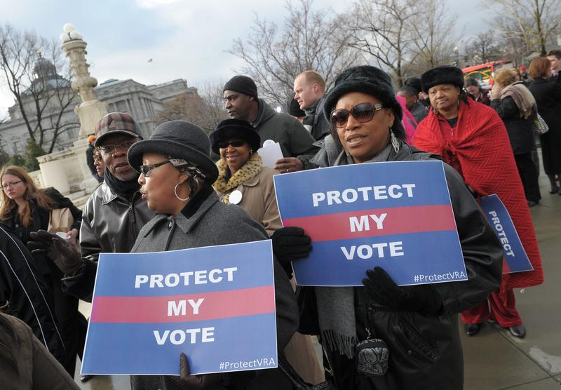 Activists hold a pro-voting rights placards outside of the US Supreme Court on February 27, 2013 in Washington, DC as the Court prepares to hear Shelby County vs Holder.