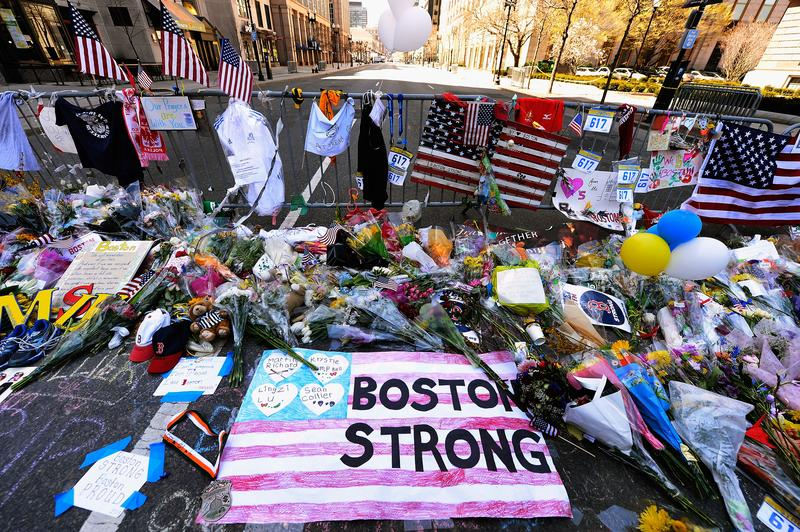 Items are placed by people visiting a makeshift memorial for victims near the site of the Boston Marathon bombings two days after the second suspect was captured on April 21, 2013 in Boston, MA.